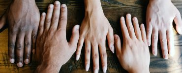 Diverse hands outstretched on table