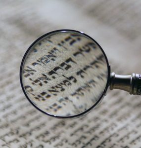 A magnifying glass enlarges Hebrew text